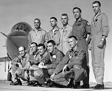 Two rows of men in front of a jet