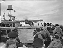 Black and white photograph of a single-engined monoplane on the flight deck of a World War II-era aircraft carrier. Large numbers of men are watching the aircraft or running towards it.