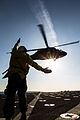 A U.S. Sailor signals the pilots of an Army UH-60 Black Hawk medevac helicopter assigned to Charlie Company, 2nd Battalion, 238th Aviation Regiment and attached to the 42nd Combat Aviation Brigade (CAB), New 131226-Z-AR422-115.jpg