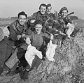 A group of cheerful men from the Royal Artillery display chickens acquired for their Christmas dinner, Venray in Holland, 24 December 1944. B13093.jpg