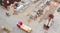 Aerial view of trucks at building yard.png