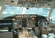 A cockpit of the 767-300ER, which exhibits a hybrid adoption of a new-generation instrument panel and analog gauges and indicators