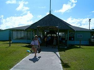 "Aitutaki Airport - Entrance to Aitutaki Airport. Note the sign ""Aitutaki International Airport"", although there are no international flights."