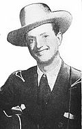 A man wearing a white cowboy hat and dark jacket, smiling broadly and holding a guitar