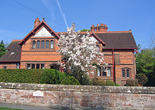 A red-brick house with two gables, one larger than the other