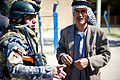 An Iraqi man speaks with an Iraqi police officer during a humanitarian aid drop in Taji, Iraq, March 2, 2011 110302-A-IN286-022.jpg