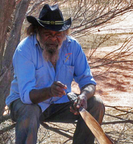 Aboriginal man sitting with black brimmed hat, holding a traditional tool