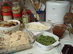 Leftovers from an American holiday meal: mashed potatoes, gravy, cranberry sauce, green beans, turkey