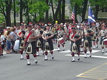 A group of men in matching outfits including kilts down a treelined road.