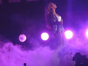 On the Run Tour: Beyoncé and Jay-Z (TV program) - Beyoncé performing in denim shorts, a white T-shirt and a studded leather jacket. The stage production for the performance consisted of heavy smoke and coloured lighting.
