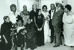 "Sippie Wallace - Performers of the ""Blues Is a Woman"" concert at the Newport Jazz Festival at Avery Fisher Hall: (standing, l to r), Koko Taylor, Linda Hopkins, producer George Wein, Rosetta Reitz, Adelaide Hall, Little Brother Montgomery, Big Mama Thornton, Beulah Bryant; (seated, l to r), Sharon Freeman, Sippie Wallace, Nell Carter (copyright Barbara Weinberg Barefield)"
