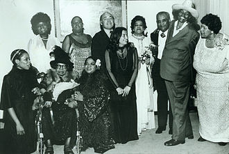 """Sippie Wallace - Performers of the """"Blues Is a Woman"""" concert at the Newport Jazz Festival at Avery Fisher Hall: (standing, l to r), Koko Taylor, Linda Hopkins, producer George Wein, Rosetta Reitz, Adelaide Hall, Little Brother Montgomery, Big Mama Thornton, Beulah Bryant; (seated, l to r), Sharon Freeman, Sippie Wallace, Nell Carter (copyright Barbara Weinberg Barefield)"""