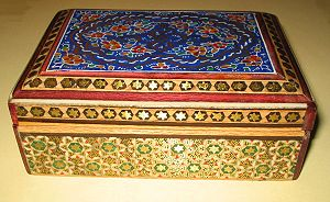 Khatam - A simple Khatam marquetry box decorated with geometric patterns of triangles and 6-point stars on its sides, and a floral design on its lid