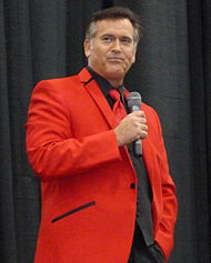 A man standing with a microphone, wearing a red blazer.