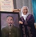 Bubush Osmonalieva with her father's picturesque portrait, in Kochkor. 07.8.2014.jpg