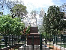 A statue in a plaza, with trees at the sides, and wires around it.