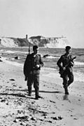 Two armed men, one with a rifle with a bayonet attached and the other carrying a submachine gun, walking along the water's edge below a line of cliffs.