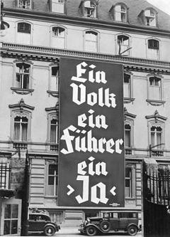 Photo noir et blanc, prise à Berlin en novembre 1933, d'une affiche électorale du NSDAP déployée sur les trois premiers étages de la façade d'un bâtiment de cinq étages (bureau du parti nazi). On peut lire, en grosses lettres, le slogan en allemand: «Ein Volk, ein Führer, ein Ja».