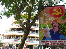 A poster showing a red sky emblazoned with the hammer-and-sickle above a stylized city landscape. In the foreground stands a light-skinned man wearing an orange hat, a blue collared shirt and cyan gloves; he holds a paper with a symbol of atomic energy in his right hand. At the foot of the poster is Vietnamese text. Behind the poster is a large, white, multi-storey building behind a tree.