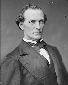A man with curly, receding black hair wearing a black jacket, vest, and bowtie with a white shirt