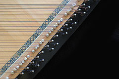 The strings are wrapped around tuning pins and rest on pegs.