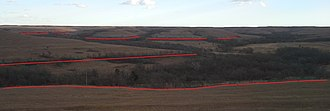 Cottonwood Limestone - Highlighted here with red lines, the boulders and moisture-seeking shrubs make the Cottonwood Limestone easy to identify and trace along the valleys within the Konza Prairie.