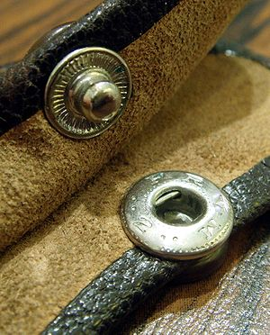 "Snap fastener - The two halves of a riveted leather snap fastener. The male half (top) has a groove which ""snaps"" in place when ""pressed"" into the female half (bottom)"