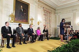Five people seated on a stage under a large portrait of Lincoln while Michelle Obama stands on the stage speaking.