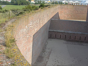 Counterscarp - Counterscarp of a Napoleon era polygonal fort (Fort Napoleon, Ostend). Counterscarps had become vertical by this time. The housing at the bottom of the ditch is a caponier from where the defenders could fire on attackers that managed to climb down into the ditch, while being protected from cannon fire themselves.