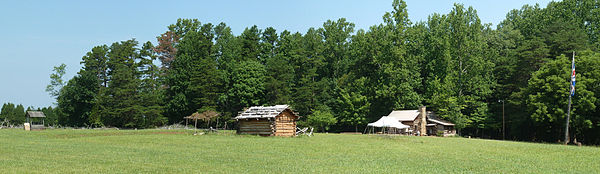 A panoramic view of the historic site showing two cabins and a well, as well as a flagpole bearing the British flag