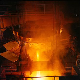 Electric arc furnace - An electric arc furnace (the large cylinder) being tapped