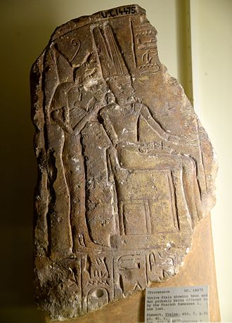 Amun - Fragment of a stela showing Amun enthroned. Mut, wearing the double crown, stands behind him. Both are being offered by Ramesses I, now lost. From Egypt. The Petrie Museum of Egyptian Archaeology, London