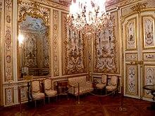 Vue de deux murs d'un cabinet décoré de boiseries blanches et de dorures, couvertes de peintures, avec quatre chaises et un canapé