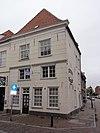 foto van Huis op de hoek van de Oliestraat, met gebosseerd gepleisterde lijstgevels en schilddak