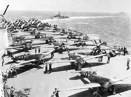 Royal Navy Fleet Air Arm aircraft warm up their engines before taking off. Other warships from the British Pacific Fleet can be seen in the background.