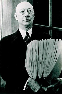 portrait of a Henry Allen Gleason, wearing a suit and glasses, holding three folders of herbarium specimens