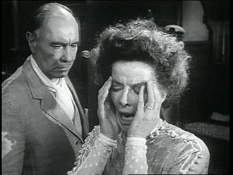 Long Day's Journey into Night (1962 film) - Katharine Hepburn as morphine-addicted mother Mary Tyrone (with Ralph Richardson as James Tyrone behind her).