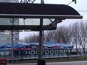 Hoofddorp - The train station and a bus station from the special bus line from Haarlem to Amsterdam, the Zuidtangent, which has largely its own bus lane, with priority at crossings. In the background, the row of trees can be seen that is planted along the Geniedijk