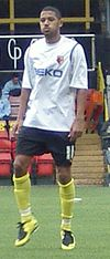 Man wearing white t-shirt, black shorts and yellow socks, standing on a pitch