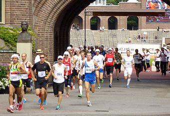 Klockan 13.48 den 14 juli 1912 gik starten for det olympiske maratonløb i Stockholm.   Alexis Ahlgren fra Trollhättan tog teten inde på Stadion.   Til højre:   Jubileumsmarathon 2012-07-14, klokken 13.50 efterlod løberne Stadion og svinger ind på Valhallavägen.