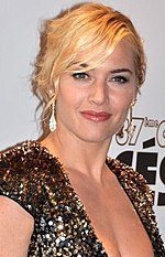 A young woman with blonde hair, pulled back from her face wears earrings and a golden sequin dress.