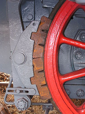 Railway brake - A traditional clasp brake: the brake shoe (brown) bears on the surface (tyre) of the wheel (red), and is operated by the levers (grey) on the left