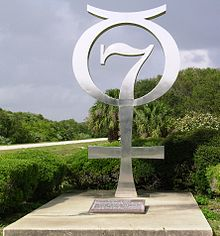 Silver memorial in the form of a combined 7 and Mercury symbol