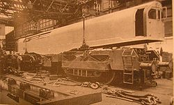 A picture of an 0-6-0+0-6-0 steam locomotive under construction. The cuboid box containing cabs and boiler is being lowered onto the two 0-6-0 bogies by a crane inside a locomotive works. Various components are scattered in the foreground.