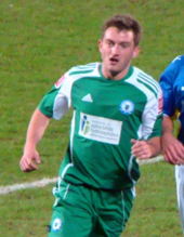 Short-haired white man wearing green and white sports kit, running on grass.