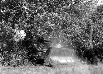 17th Armored Engineer Battalion - M4 Sherman tank mounted with M1 bulldozer blade makes its way through a hedge in France, 1944