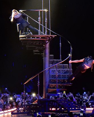 """Rebel Heart Tour - Madonna performing """"HeartBreakCity"""" on top of the steel spiral staircase."""
