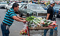 Man carrying vegetables from a cart on the street.jpg
