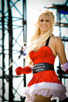 A Caucasian woman with blonde hair smiles while wearing a red dress with a white fur trim, in the style of Santa Claus. She is wearing elbow-length red gloves, also with a fur trim, and a black belt around her waist.