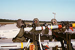 Members of a munitions crew from the 33rd Tactical Fighter Wing lift an AIM-9 Sidewinder missile from a rack during Nomad Thrust, a chemical warfare exercise designed to test the wing's readiness in case DF-ST-87-12-569.jpg